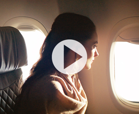 A woman excitedly staring out the aircraft window in anticipation of the journey ahead.